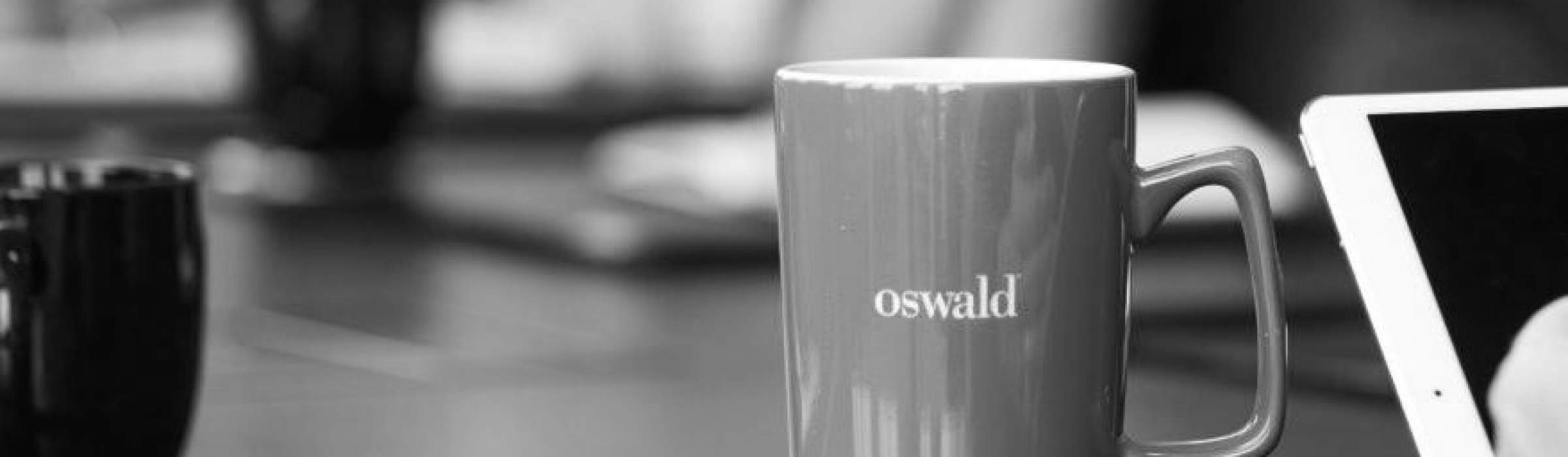 Red Oswald coffee mug on a conference table