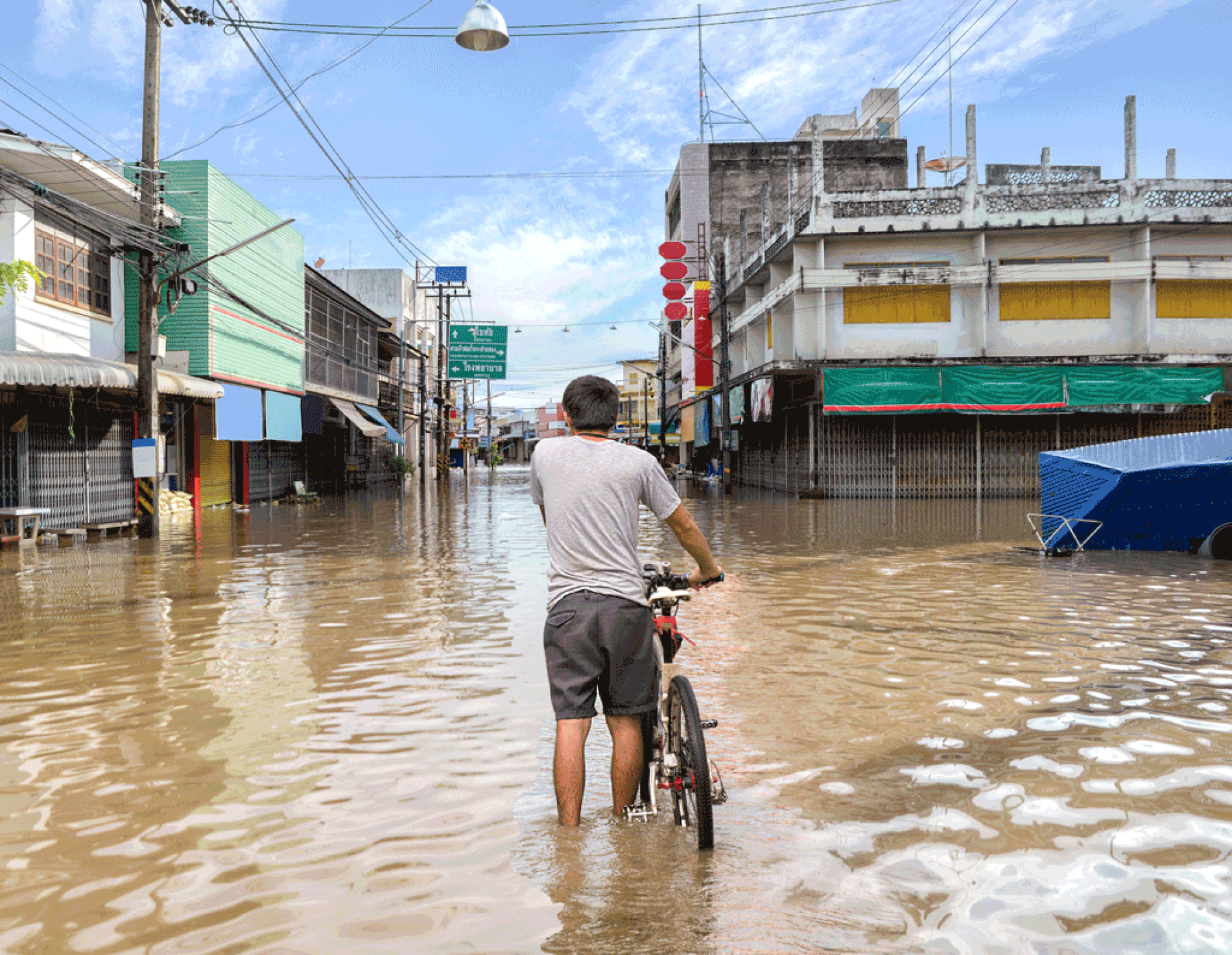 Man walking with a bike through a flooded street