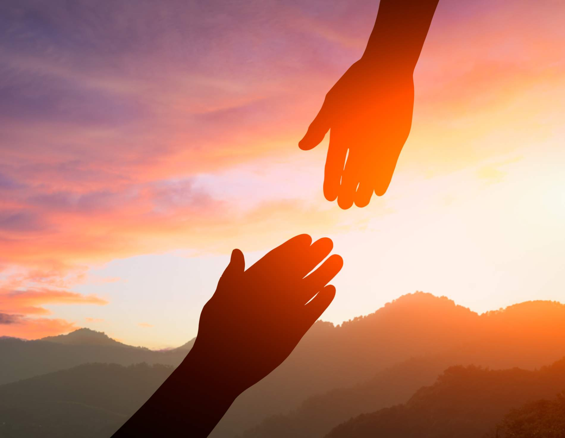 Hands reaching towards each other in front of a sunset