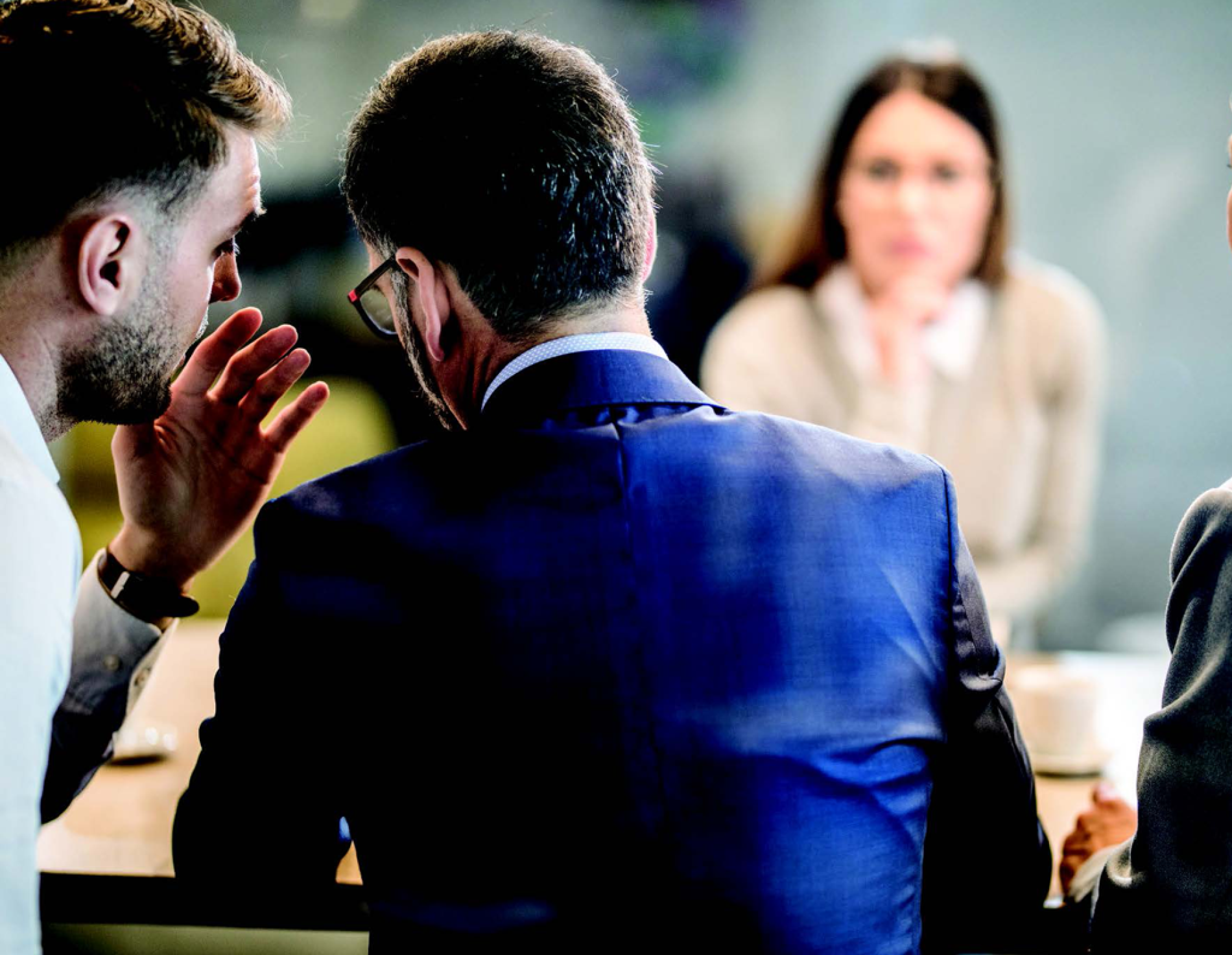 Man at a conference table whispering to another man's ear