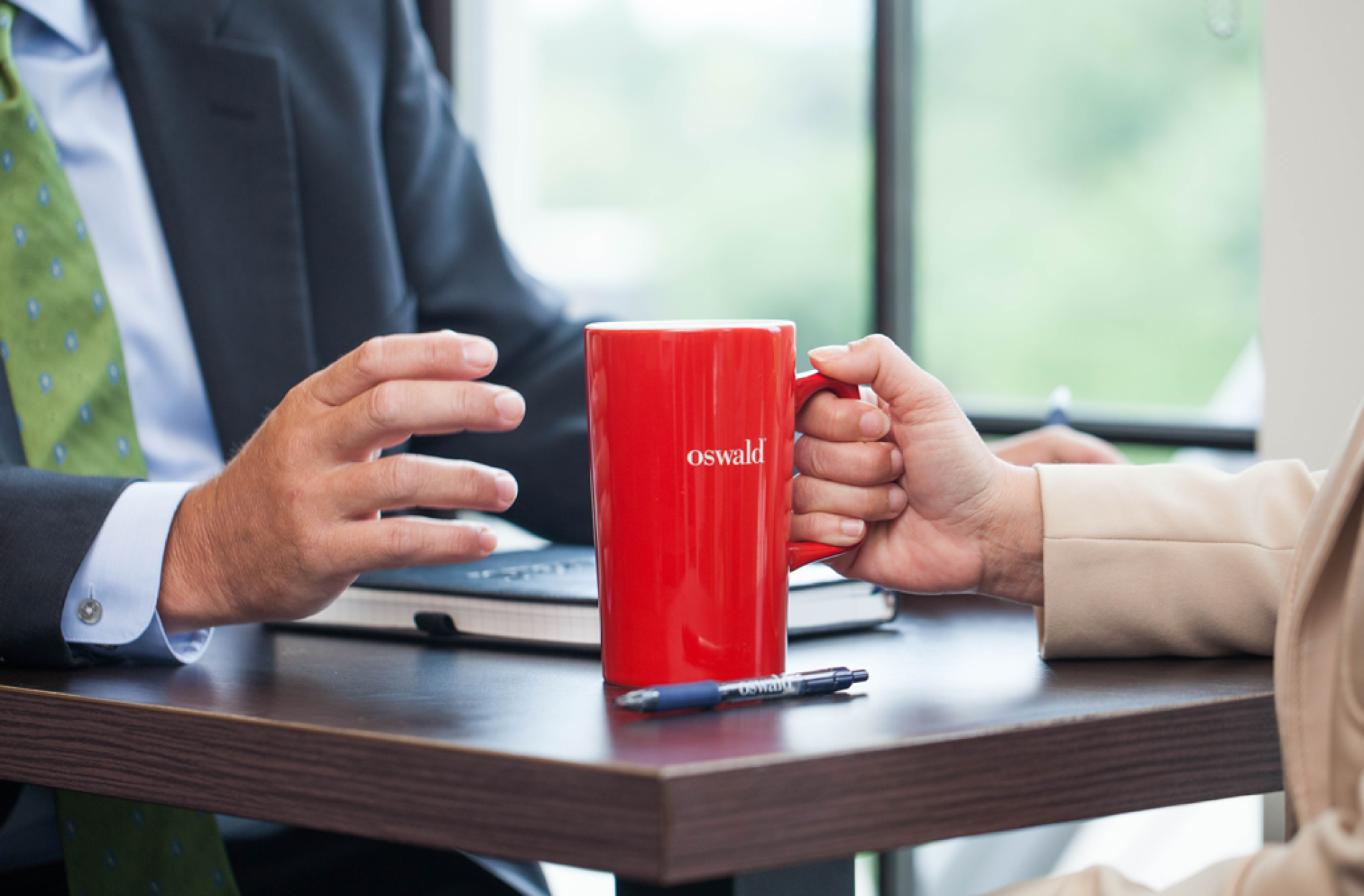 Hand holding a red mug on a table