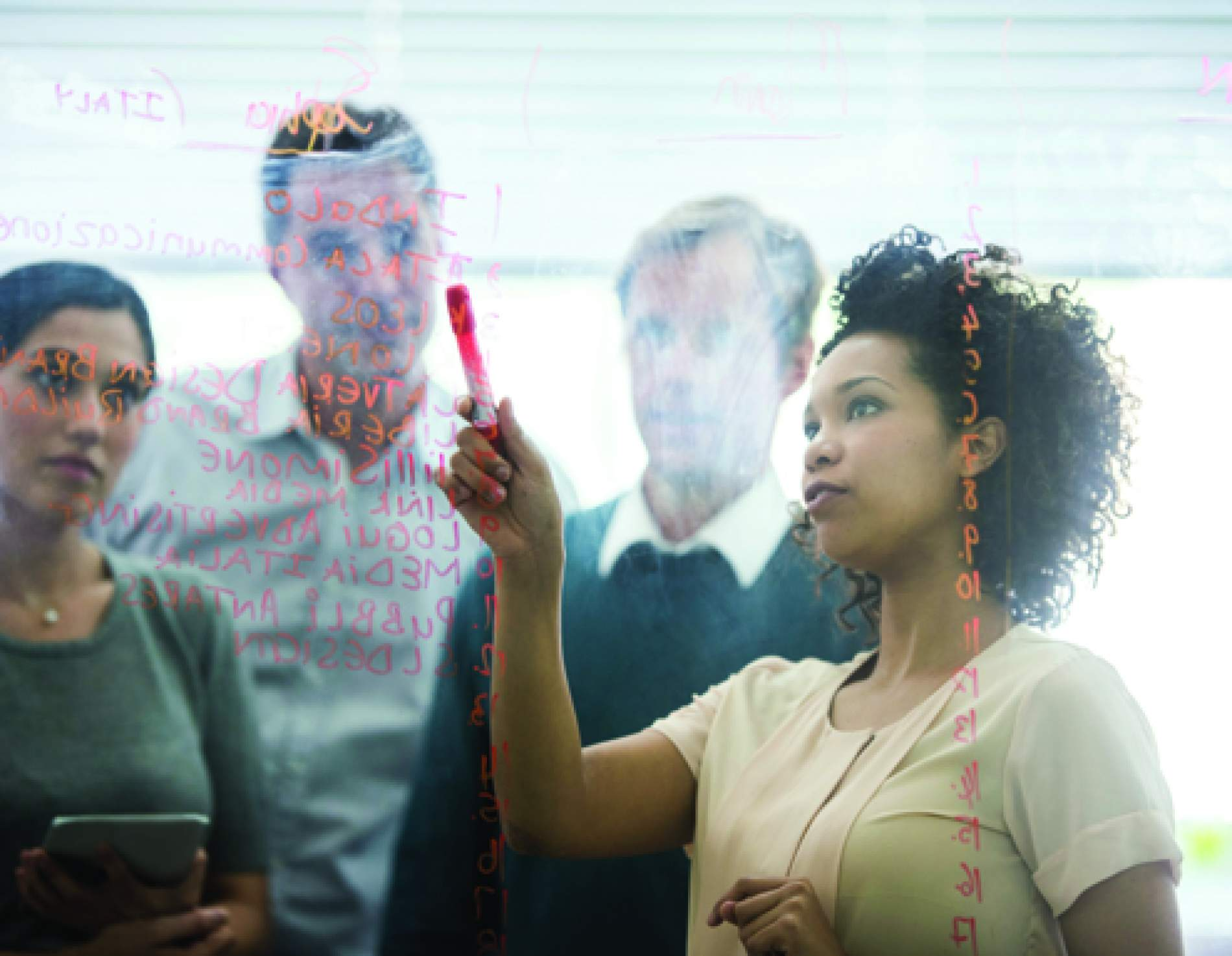 People looking at data analytics on a glass