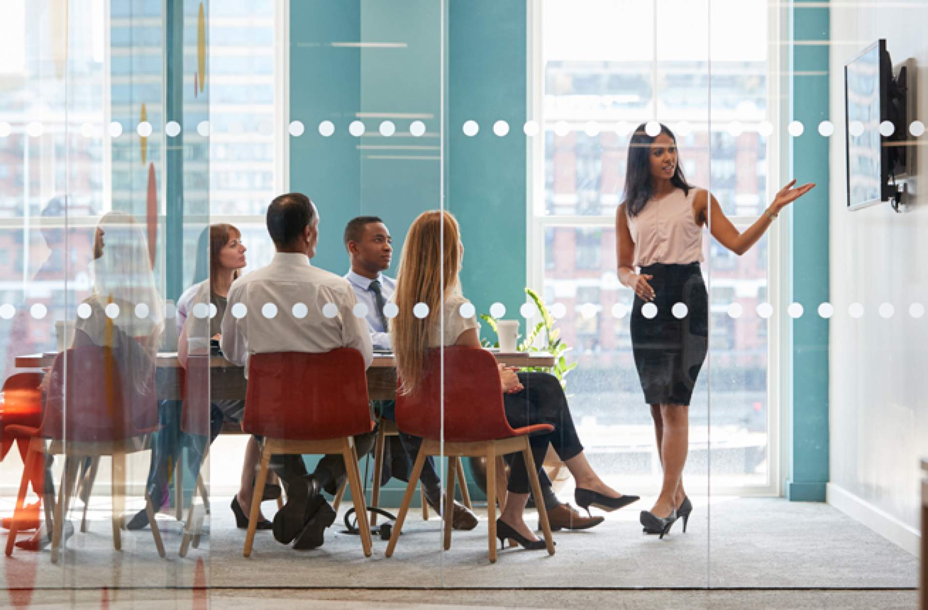 Woman giving a presentation in a conference room full of people