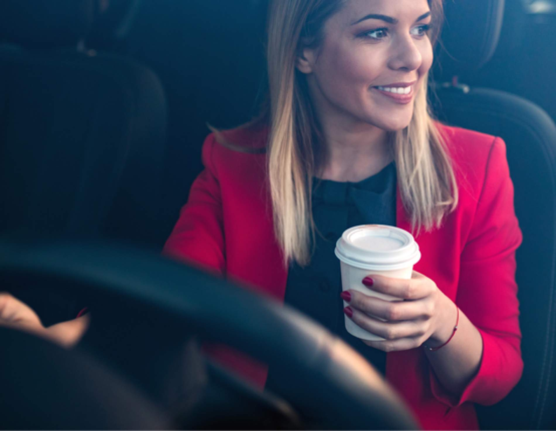Woman driving with coffee in her hand