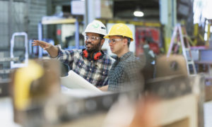 Multi-ethnic workers talking in a manufacturing plant